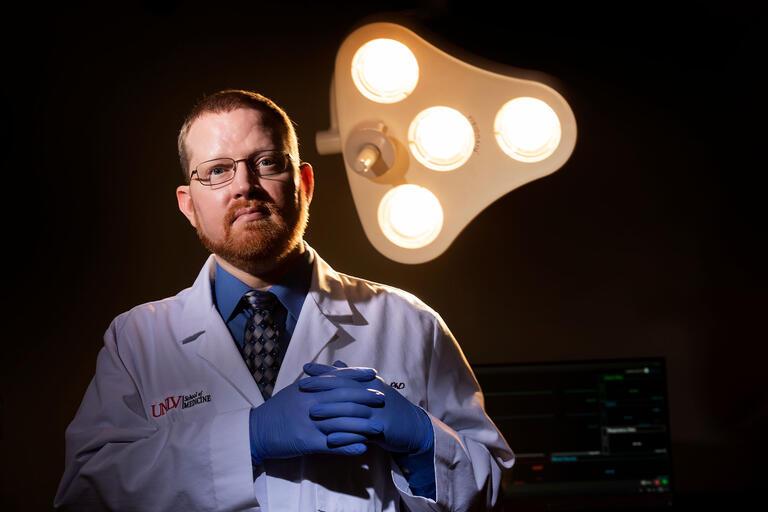 Man in doctor coat in front of lights.