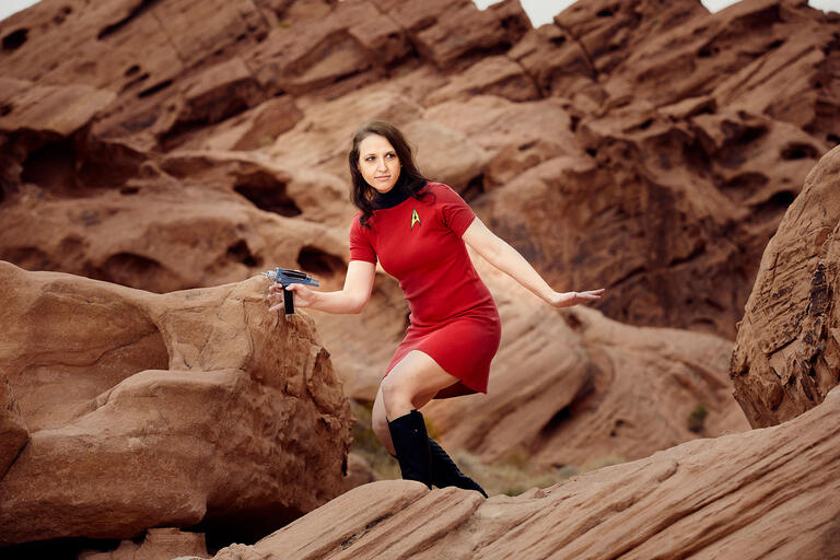 Lindsay J. Russell dressed in a red Star Trek uniform while standing on a rock formation.