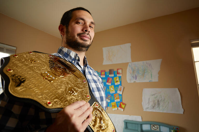 Michael Chin with his replica wrestling championship belt.