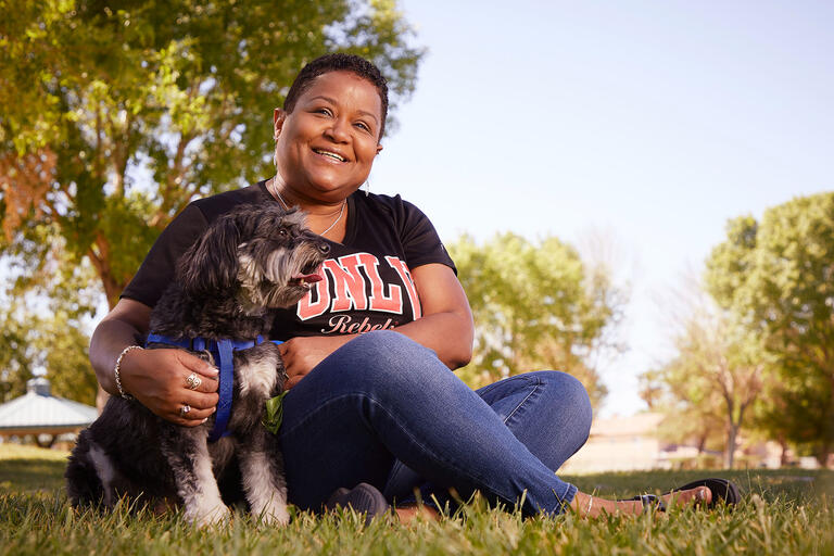Michele Washington, Claims Administration Coordinator for Risk Management & Safety with Aries, herMaltese Poodle mix in a park.