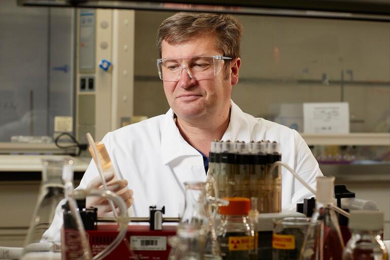 Art Gelis, Associate Professor, Director, Radiochemistry Program working with lab equipment.