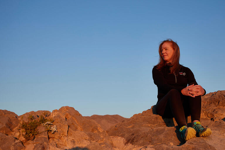 Tina Elkins sitting on a rock looking at the rising sun.