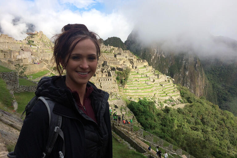 A woman stands in front of Machu Picchu