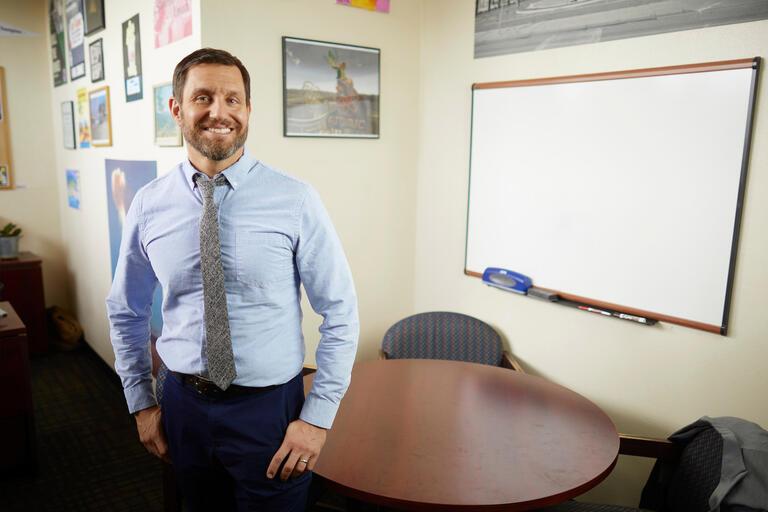 A man smiles next to a whiteboard