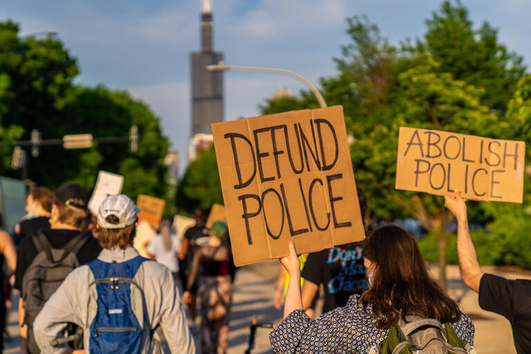 "Protest signs read ""Defund Police"" and ""Abolish Police"""