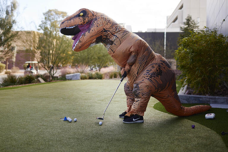 man in dinosaur costume on a putting green