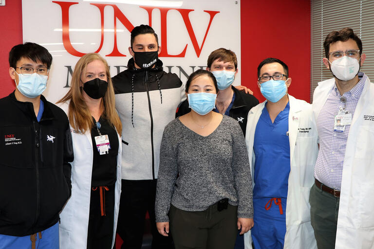 A group of doctors and a patient stand in front of a UNLV Medicine sign