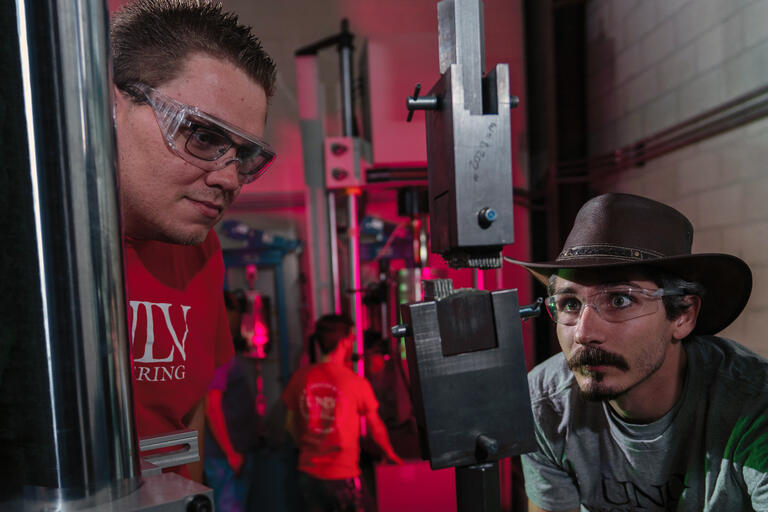 A UNLV student wearing goggles, and one wearing a hat and glasses, stare at materials in a vice.