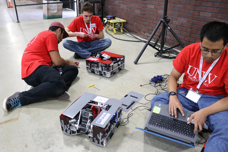 Engineering students use a laptop and tools to fix two box-like robots