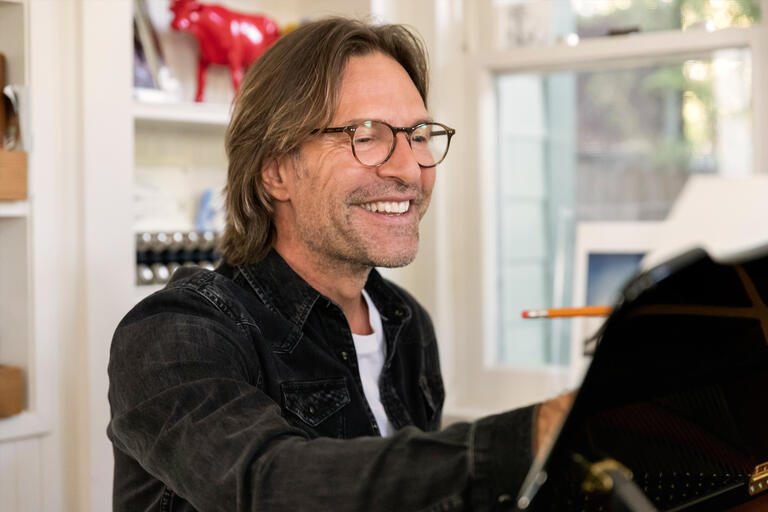 A man smiles while writing music