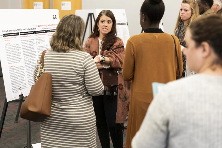 woman leading discussion at poster presentation