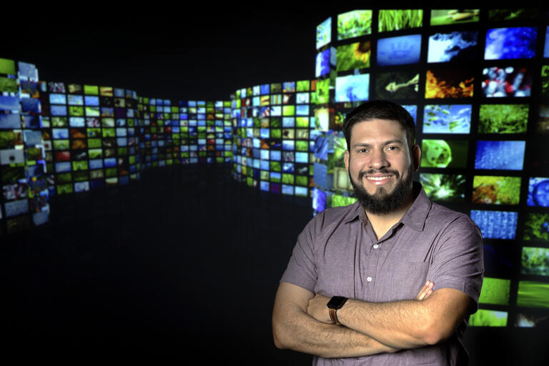 Carlos Flores stands in front of a bank of television screens