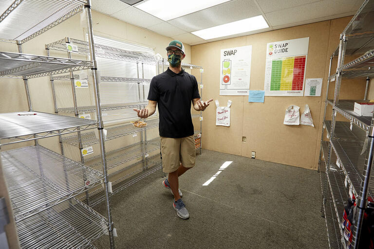a man wearing a covid-appropriate face mask gestures at empty metal shelves