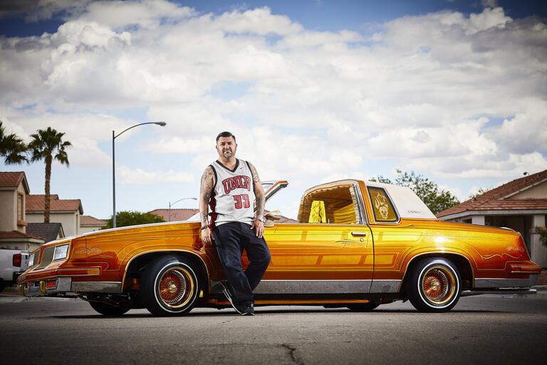 A man in a UNLV basketball jersey leans on a gold-colored Oldsmobile.