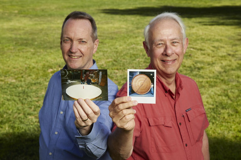 two men holding old photos