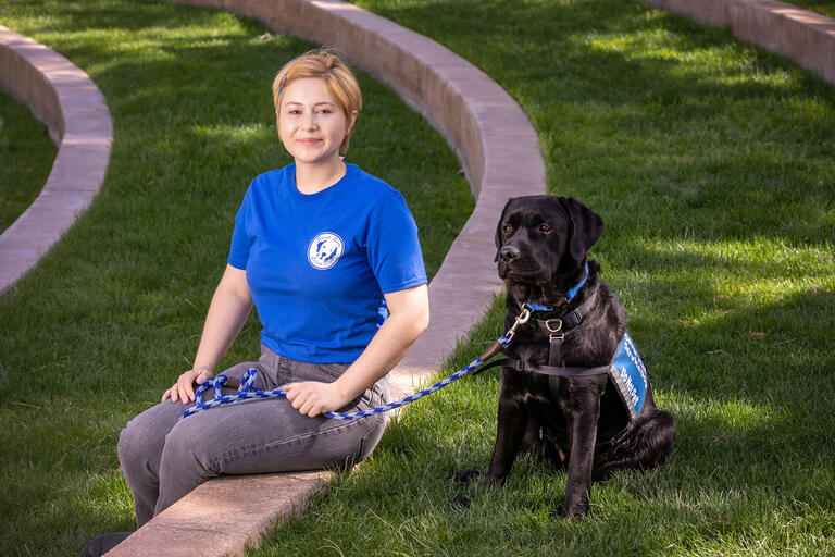 woman with Black Labrador wearing service animal vest