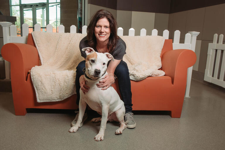 A woman sits on a couch holding on to a large dog