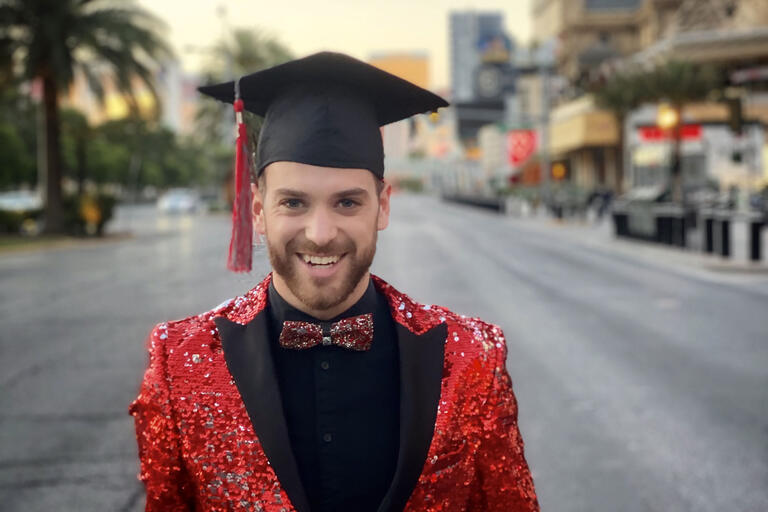 Ryan wears a black grad cap and a sequin jacket standing on an empty Las Vegas strip.