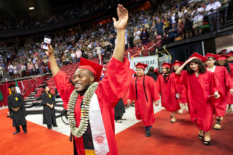 A student raises his arms in celebration at commencement