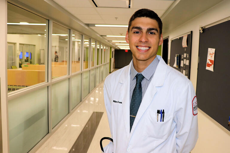 man in doctor's coat in hospital hallway