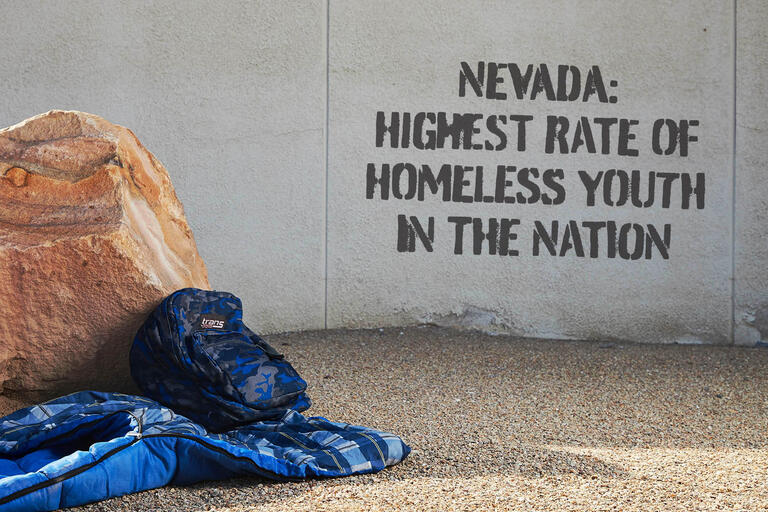 "backpack and sleeping bag next to wall with ""Nevada: Highest Rate of Homeless Youth in the Nation"" spray painted on it"