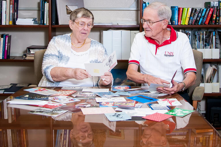 couple at desk filled with holiday cards