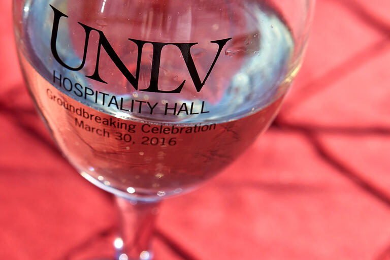 Overhead view of a glass of water with UNLV logo on it.