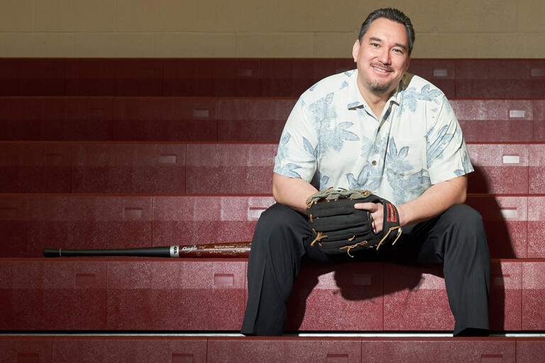 A man sits on bleachers wearing a baseball glove, with a baseball bat resting beside him