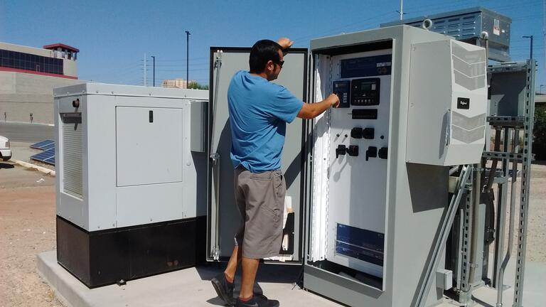 A UNLV grad student attends to a power station.