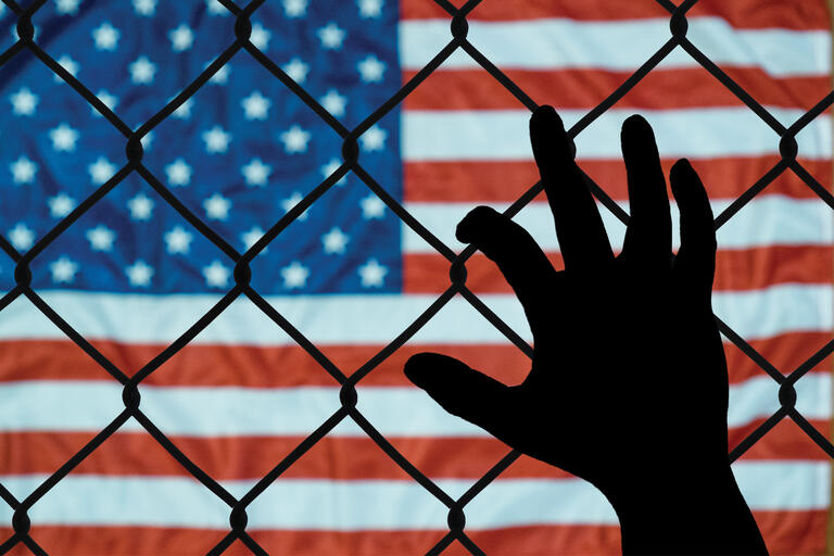 A hand reaches up to a chain link fence in front of the American flag.