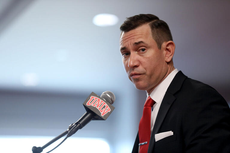 Man at microphone with UNLV logo