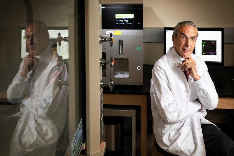 A scientist in a white lab coat rests his hand on his chin