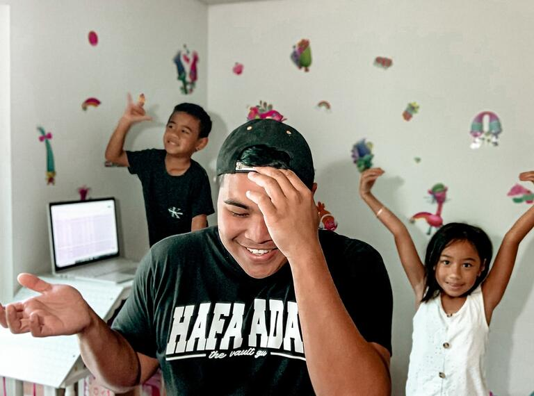 man in child's bedroom with two kids dancing behind him