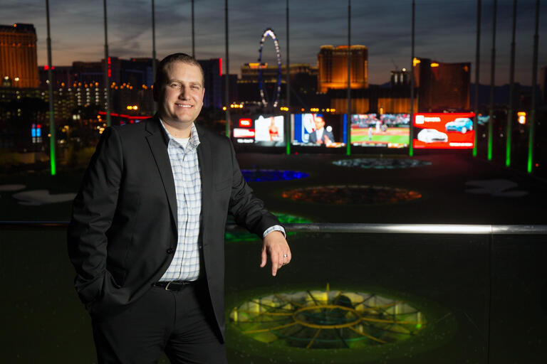 A man stands at a driving range, with a view of the Las Vegas Strip behind him