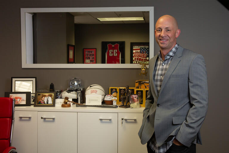 A man in a gray jacket stands in front of UNLV memorabilia
