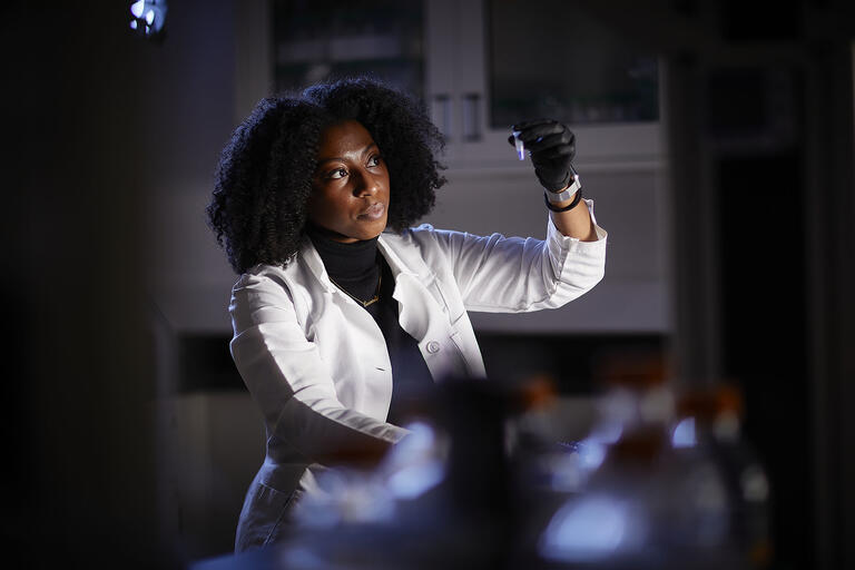 woman in lab coat looking at a sample