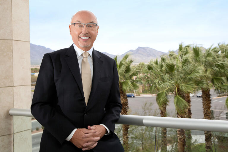 A man in a suit stands on a balcony overlooking the desert
