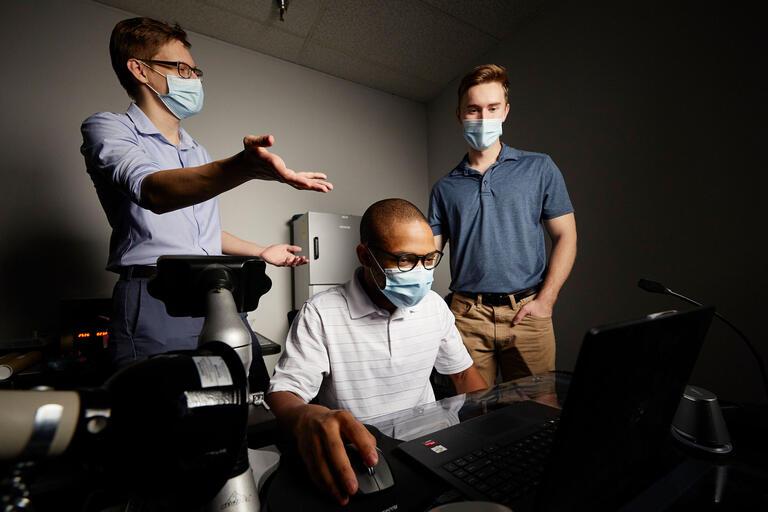 Three men crowd around a computer