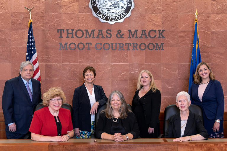 Seven law professors pose at the bench in the Thomas & Mack Moot Courtroom between the United States and Nevada flags.