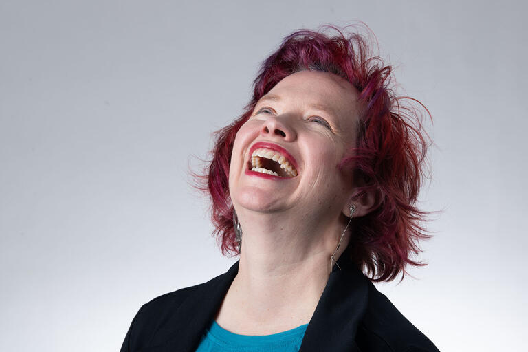 Close-up of Lisa Danielson with her head thrown back, laughing.
