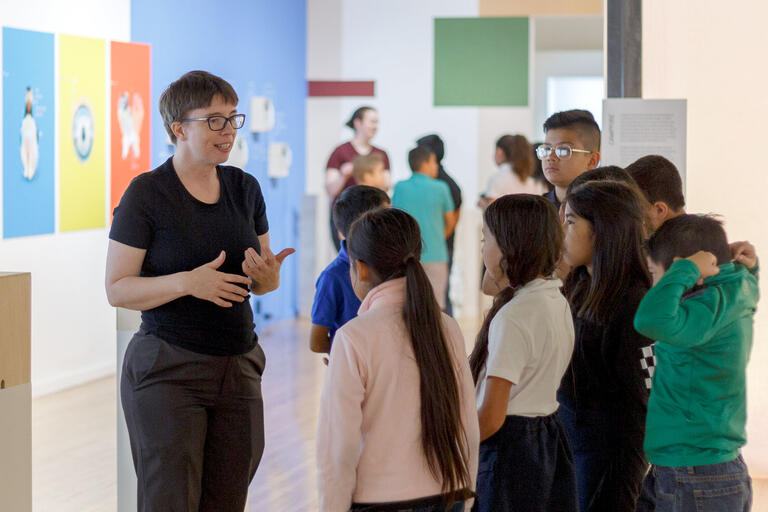 woman leading group of children through gallery