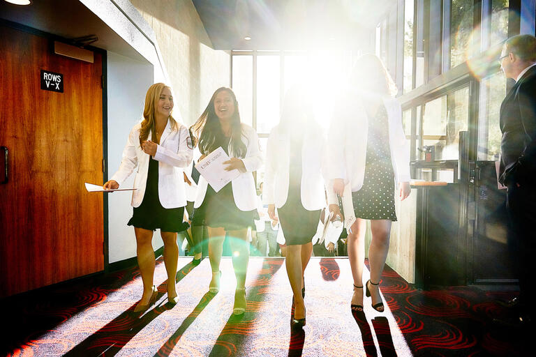A group of medical students walk down a sunlit hall