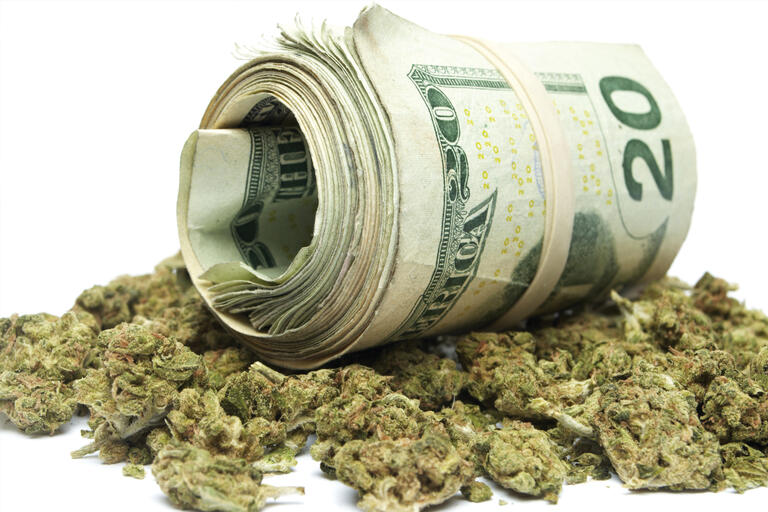 A roll of $20 bills sits on top of a pile of marijuana