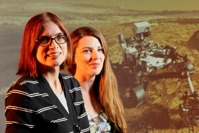 Two women stand in front of an image of a Martian rover