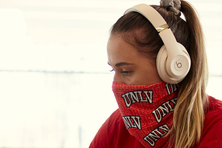 A woman in a UNLV mask
