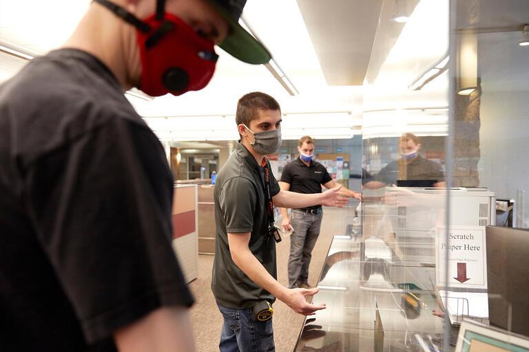 Three workers in masks install plexiglass