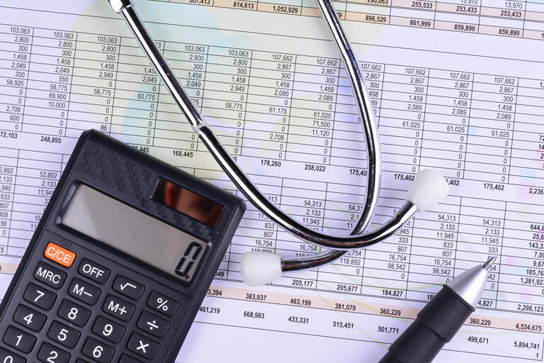 A calculator and stethoscope atop a spreadsheet