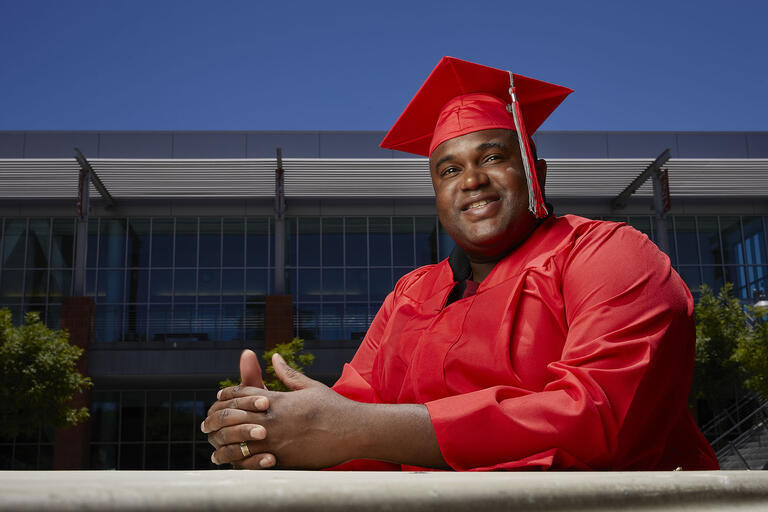 man in graduate cap and gown pictured outdoors