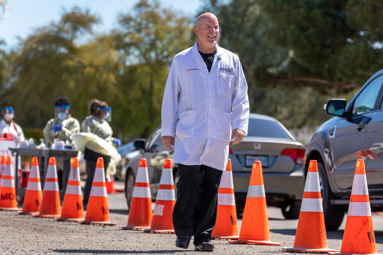 A doctor in a white lab coat walks past a row of orange cones and a line of cars.
