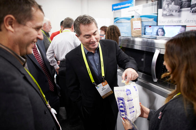President Len Jessup eating a piece of popcorn at the CES convention